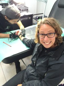 Cringing at the pain of getting a tattoo
